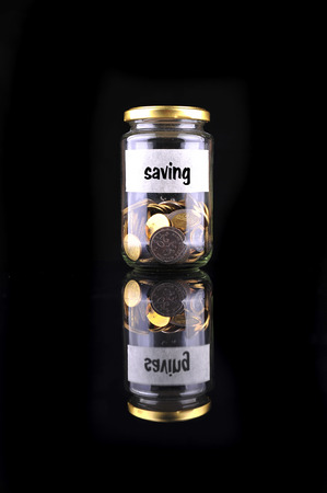 saving tips: Coins in bottle with label Saving isolated on black background - financial concept