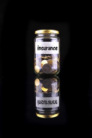 saving tips: Coins in bottle with label Insurance isolated on black background - financial concept