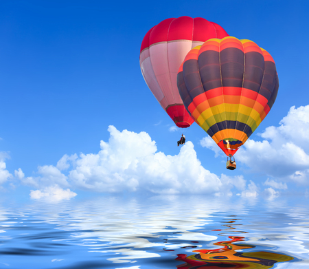Colorful Hot Air Balloons in Flight over blue sky with water reflection Stock Photo