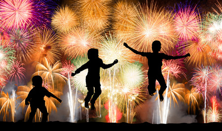 Silhouette of kids jumping over colorful firework