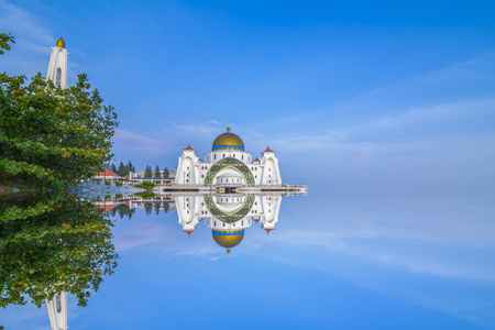 straits: Dramatic sky & reflections at Straits Mosque, Malacca. Nature composition.Motion Blur and Soft Focus due to Long Exposure. Vibrant Colors Stock Photo
