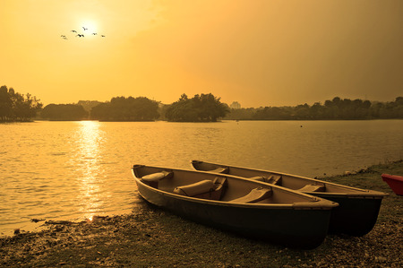 Sunset and old wooden fishing boat near the summer lake shore Archivio Fotografico