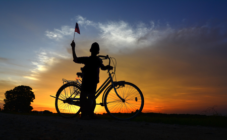 Silhouette boy holding the malaysia flag during dramatic sunset