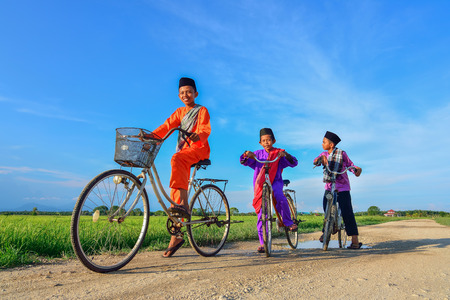 happy young local boy riding old bicycle at paddy field