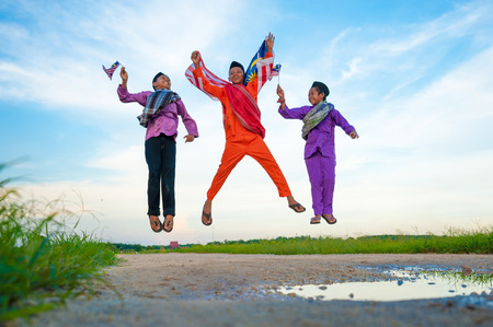 Independence Day concept - Three happy young local boy jumping at paddy field holding a Malaysian flag Stock Photo