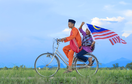 independence Day concept - Two happy young local boy riding old bicycle at paddy field holding a Malaysian flag Imagens