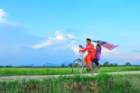 niños en bicicleta: concepto del Día de la Independencia - Dos feliz muchacho joven local monta la bicicleta vieja en el campo de arroz con una bandera de Malasia