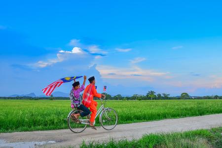 Concepto del Día de la Independencia - Dos feliz muchacho joven local monta la bicicleta vieja en el campo de arroz con una bandera de Malasia Foto de archivo - 64176998