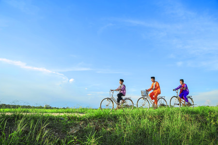aidilfitri: happy young local boy riding old bicycle at paddy field