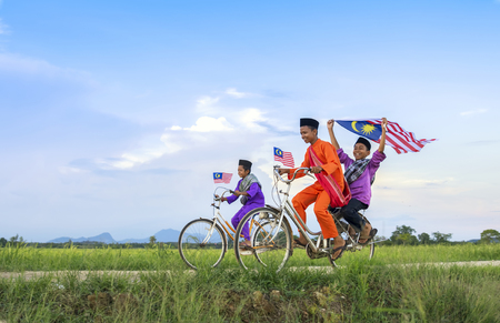 independence Day concept - Two happy young local boy riding old bicycle at paddy field holding a Malaysian flag Standard-Bild