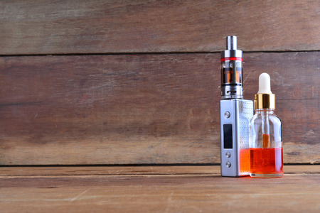 cig: E-cigarette or vaping device with liquid on wooden background