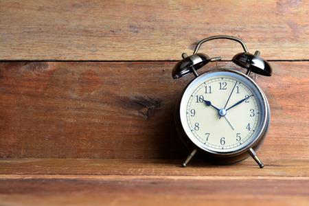 Retro alarm clock on wood background
