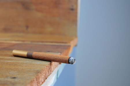 carcinogen: Burning handmade luxury Cuban cigar on an old wooden background with copyspace Stock Photo
