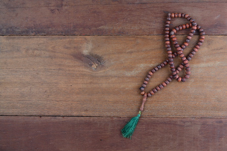 close up of wood tasbih with blur bokeh on wooden background. Wooden rosary Stock Photo