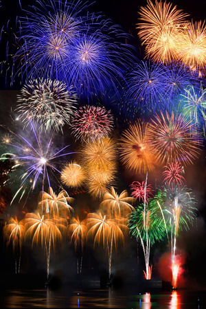 Colorful fireworks. Fireworks are a class of explosive pyrotechnic devices used for aesthetic and entertainment purposes. Visible noise due to low light, soft focus, shallow DOF, slight motion blur Stock Photo