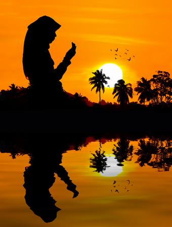 mujeres orando: silhouettes of a women praying during sunset