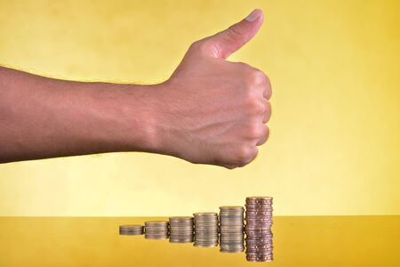 Thumb-up sign on stack of coins