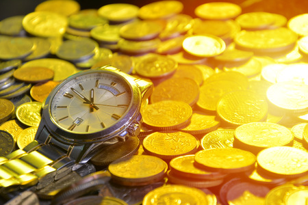 clock and stacks of coins : time - money Stock Photo