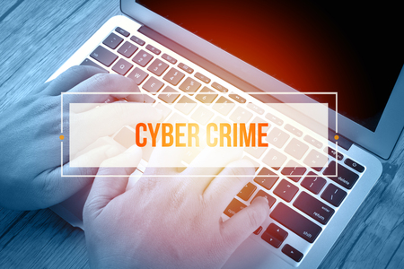 Hand Typing on keyboard with text CYBER CRIME