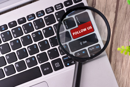 microblogging: FOLLOW US word written on keyboard view with magnifier glass