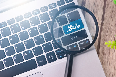 bill payment: BILL & PAYMENT word written on keyboard view with magnifier glass Stock Photo