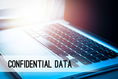 secret code: Laptop with sunlight and text CONFIDENTIAL DATA