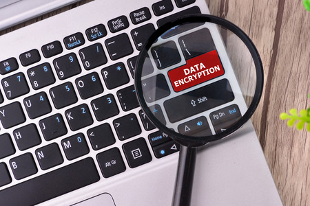 cypher: DATA ENCRYPTION word written on keyboard view with magnifier glass Stock Photo