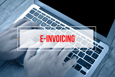 Hand Typing on keyboard with text E-INVOICING