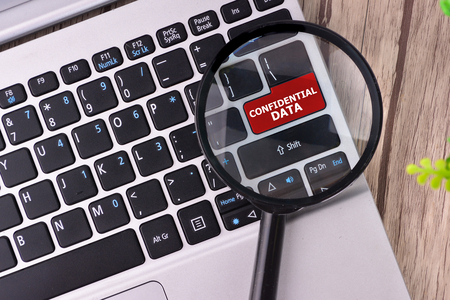 secret code: Confidential Data word written on keyboard view with magnifier glass Stock Photo