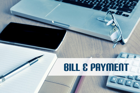 bill payment: Notebook with calculator, keyboard and pen on table with text Bill & Payment