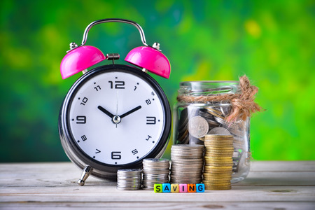 Alarm clock, Coins and cube dices with word Saving Reklamní fotografie