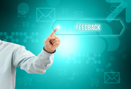 Business man touch a button on an imaginary screen with text FEEDBACK Stock Photo