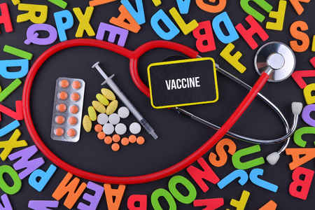 Pills, Syringe and Stethoscope with alphabet and text Vaccine Stock Photo