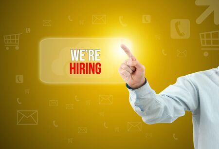 recruit help: Business man touch a button on an imaginary screen with text WERE HIRING