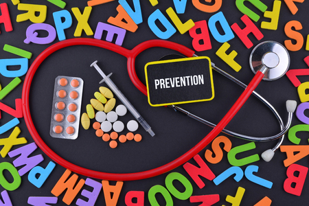 Pills, Syringe and Stethoscope with alphabet and text Prevention Stock Photo