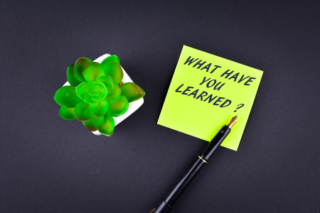 recap: Green sticky note with pen with text What have you learned ? Stock Photo