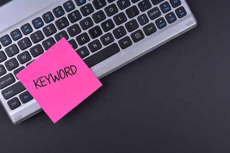 Sticky note on keyboard with text KEYWORD
