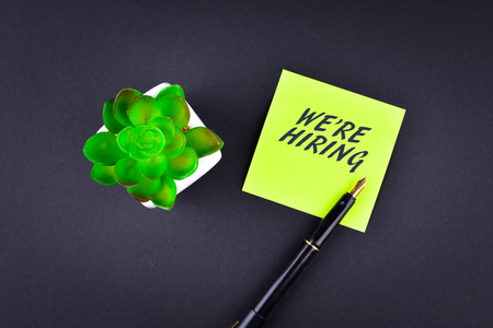 submit search: Green sticky note with pen with text WERE HIRING