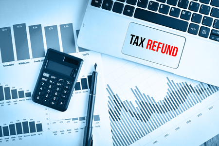 exemption: Graphs, charts and keyboard with text TAX REFUND