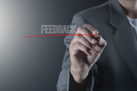 criticize: Hand of business man write or writing text FEEDBACK Stock Photo