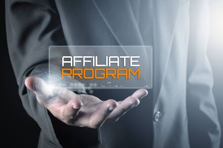 Hand holding transparent screen with text AFFILIATE PROGRAM