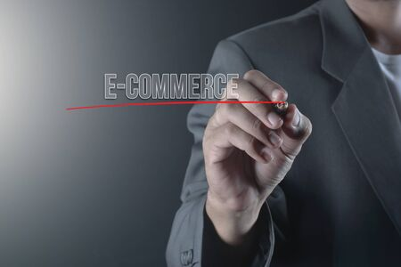 Hand of business man write or writing text E-COMMERCE