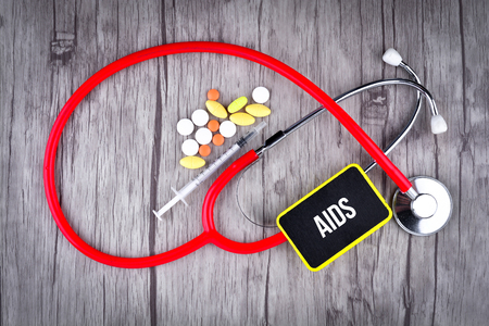 Pills, Syringe and Stethoscope with text AIDS