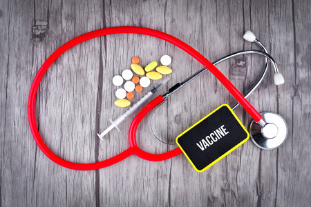 Pills, Syringe and Stethoscope with text Vaccine