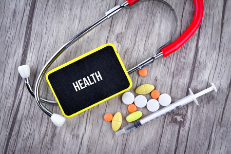 Pills, Syringe and Stethoscope with text Health