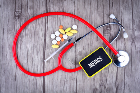 Pills, Syringe and Stethoscope with text Medics Stock Photo