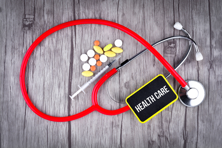 Pills, Syringe and Stethoscope with text Health Care