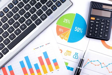 Laptop and pen with business charts, graphs, statistic and documents background for education and business concepts Stock Photo