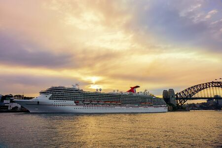 SYDNEY, AUSTRALIA - JULY 17 2018 : The ocean cruise liner is docked at the Overseas Passenger Terminal in Sydney Harbour, Circular Quay with sunset view over sydney bridge
