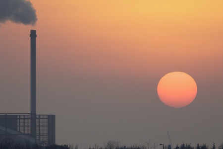 A tall chimney spews out smoke as the sun sets in the smog.